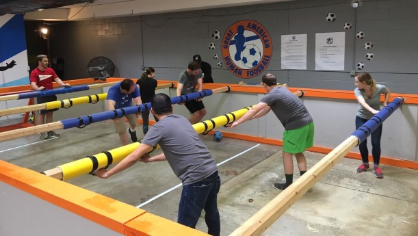Bonfyre employees team-build during a human foosball game.